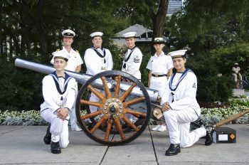 Canadian Navy Unit in white uniform smiles for camera beside cannon.
