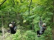 Two women on a zipline looking back and smiling