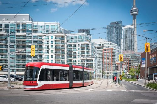 New, red Toronto streetcar - building and CN Tower in background