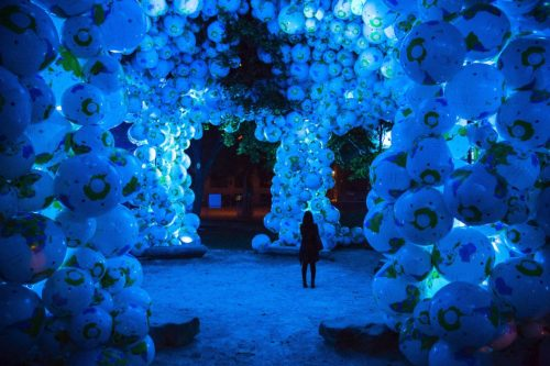 Person walking through exhibiton filled with blow up balls. Exhibition from 2014 Nuit Blanche - 'Walk Among Worlds'