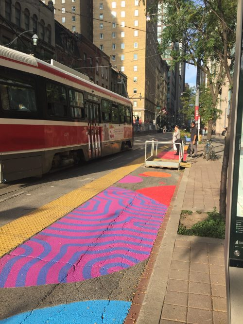 Road murals at the streetcar stop at King and Church. Streetcar is stopping in this photo and someone is waiting to get on the streetcar.