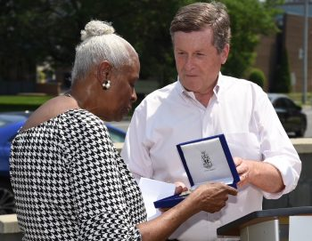 Mayor John Tory hands Pat Moore her key to the City in Throncliffe.