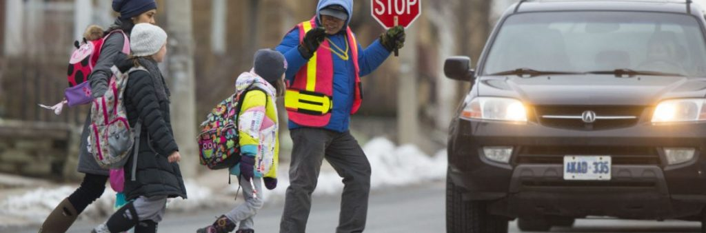 Image of a school crossing guard helping 3 children cross the street safety
