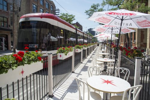 Streetcar passing by curb lane cafe with seating and umbrellas