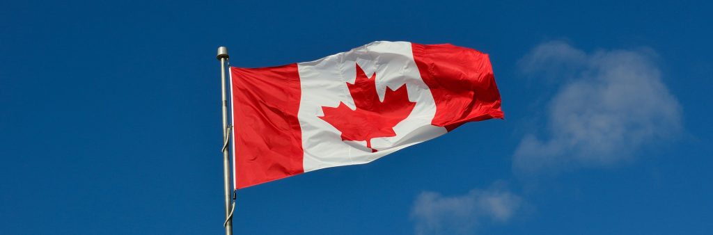 Canadian flag flying in breeze in front of blue sky