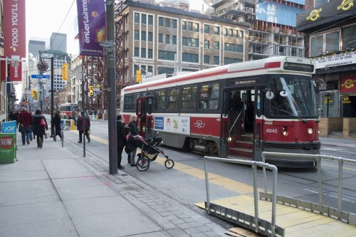 Streetcar stopped at TTC stop with accessibility ramp and people waiting to get on streetcar