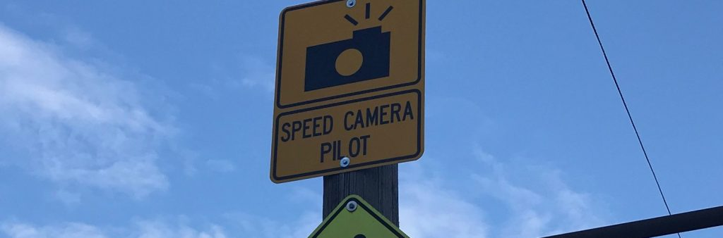 Image of a yellow sign reading speed camera pilot