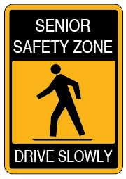 Yellow and Black sign with a man walking that reads senior safety zone, drive slowly.