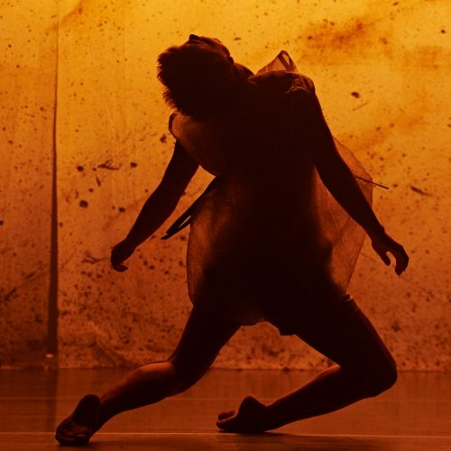 Dancer on knees - in shadow. Orange/golden background