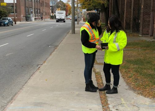 Image of two people in safety vests inspection the sidewalk