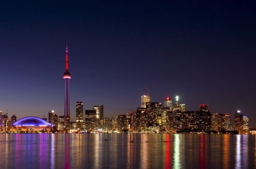 Toronto skyline from island - multi coloured lights reflected in water