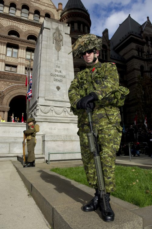 Two Canadian soldiers stand in honour guard at the Old City Hall cenotaph.