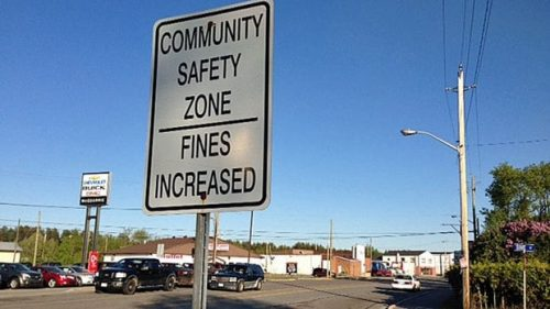 """Image of black and white street sign, reading """"community safety zone, fines increased"""""""