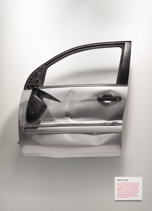 A dented minivan door is suspended in mid-air like an exhibit in an art gallery.