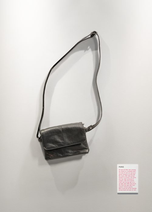 A small purse with straps is mounted on the wall like an exhibit in an art gallery.