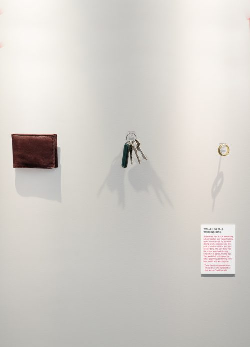A wallet, a set of keys and a man's wedding ring are mounted on the wall like an exhibit in an art gallery.