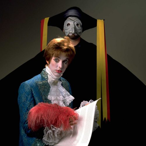 Man dressed as Mozart. Mask and cape in background.