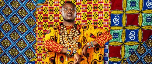 Obaaberima artwork. Man in front of multi coloured African tapestries