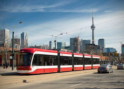 New streetcar (red) at stop. CN Tower in background.. Car in foreground