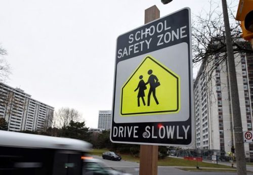 """Image of street sign in black, white and yellow reading """"School safety zone, drive slowly"""""""