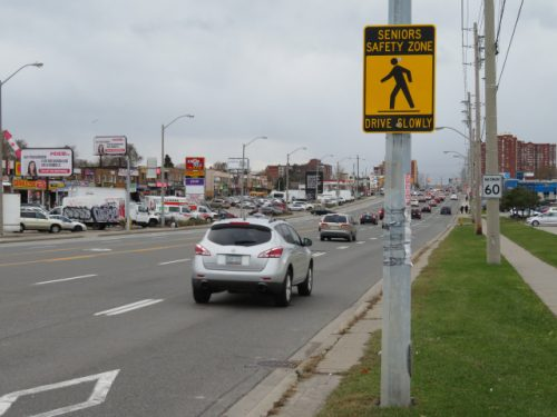 """Image of a yellow and black street sign, reading """"Senior Safety Zone, drive slowly"""""""