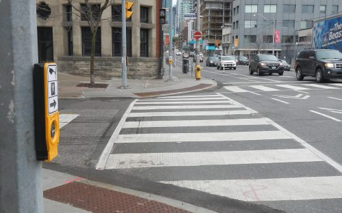 Image of a intersection with zebra crossings and an accessible pedestrian signal.