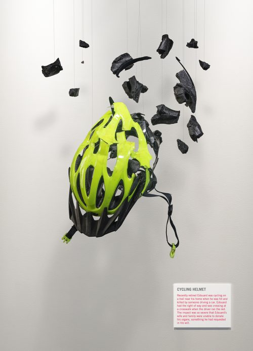 A damaged cycling helmet is suspended in mid-air like an exhibit in an art gallery. Small fragments hang around the helmet appearing to be frozen in mid-air.