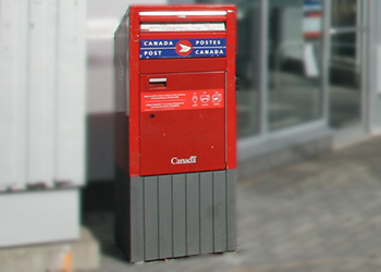 Canada Post mailbox on a city street on a sunny day
