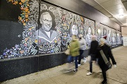 Blurry images of people walking by street art.