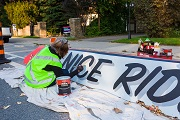 A City worker painting a sign that reads have a nice ride.