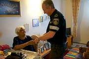 A paramedic talks to an elderly woman in her home.