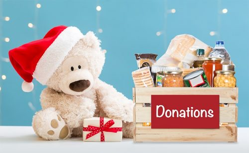 A teddy bear wearing a Santa hat sits with a wrapped gift and a box full of non-perishable food items with a Donations sign on it.