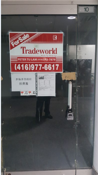 View of entry way to 222 Spadina Avenue with for sale sign. Unit 10 is located one level below street level