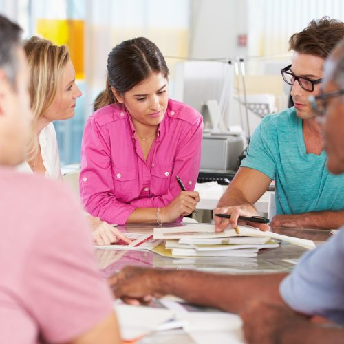 A group of people sit around a table discussing a matter.