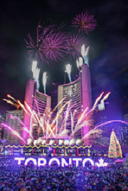 Spectacular fireworks going off at midnight at Nathan Phillips Square over the Christmas tree, skaters and the Toronto sign.