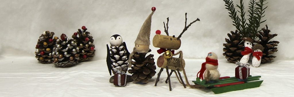 Handcrafted pine cone elf, cork reindeer and felted snowman delivering a gift to a pine cone penguin figure.