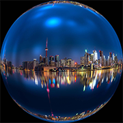 Circular image City of Toronto skyline and reflection on water at night.