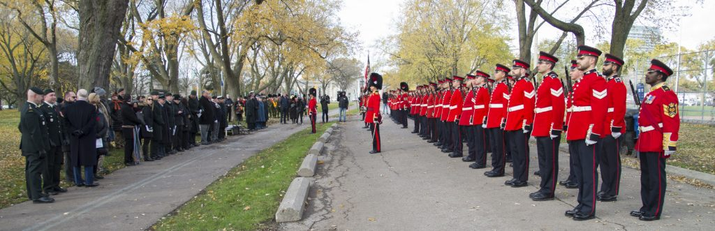 Soldiers in red uniform salute the Mayor and Lieutenant Governor in Coronation Park
