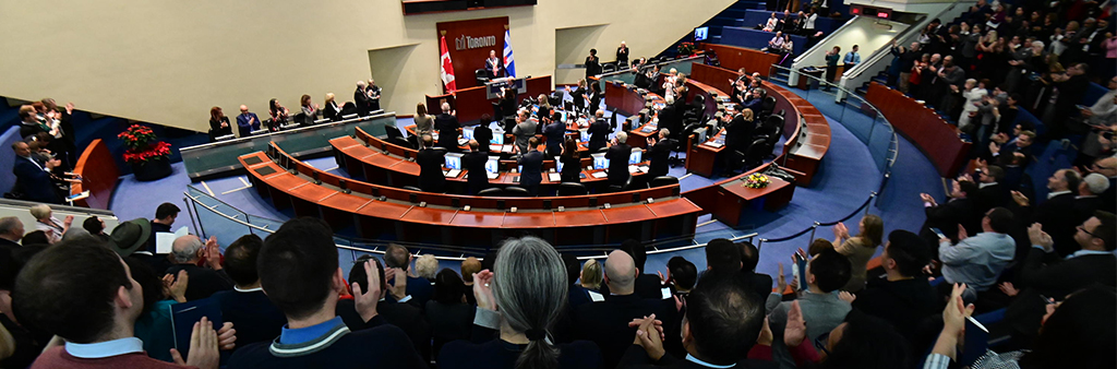 Members of the public and City Councillors clap after Mayor John Tory receives the Chain of Office during the First Meeting of Council of December 4, 2018. Image is taken from the top row of the public seating and looks down at the council floor.