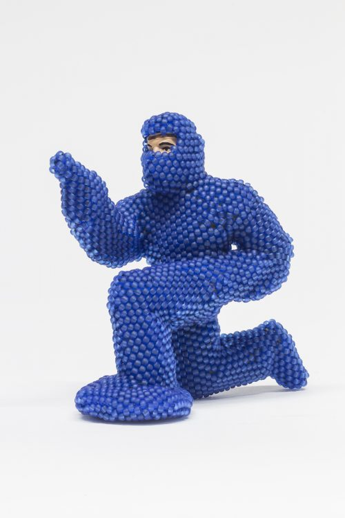 Image info: Bev Koski, Ottawa #1 (2014), 8 x4.5 x8.5cm. human figure in blue, bubble wrap, full body suit. crouching, pointing.