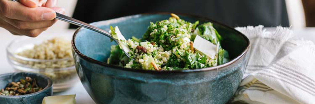 Hand with fork digging into a blue bowl with kale and quinoa salad.