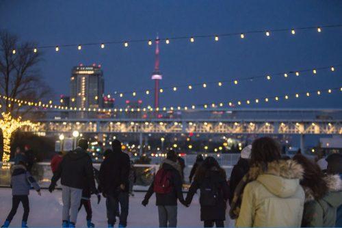 Strings of lights. CN Tower in background. People skating