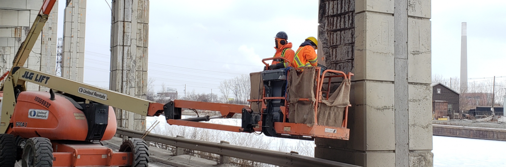 Construction workers in a cherry picker lift performing maintenance work on a Gardiner bent
