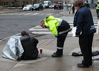 Street outreach worker in high visibility vest talks to homeless man sitting on the sidewalk.
