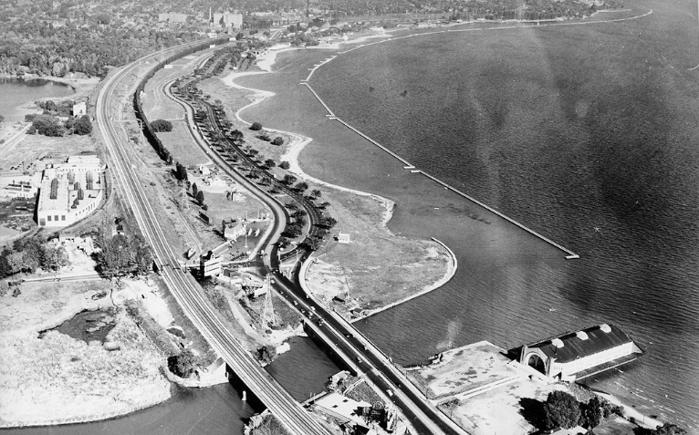 An old photograph from the late 1950s shows an aerial view of the newly build Gardiner Expressway snaking eastbound from approximately Sunnyside Pavillion to Toronto's downtown.
