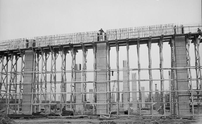 Construction workers can be seen working on top of a highway bent during the construction of the Gardiner