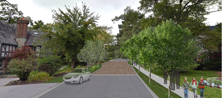 Riverside Drive, wide street with sections of interlocking pavers and a sidewalk on the right side. The street is lined with trees