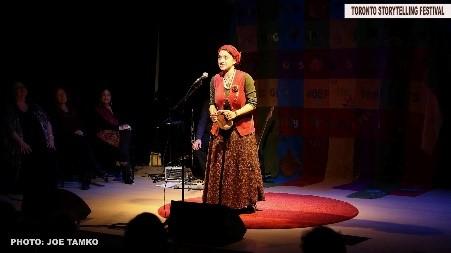 Storyteller at mic on stage