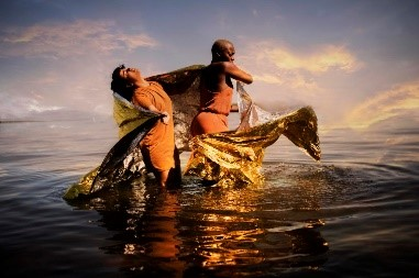 Photo info: No Woman's Land, credit: Zahra Saleki. People dancing, wrapped in gold cloth. in water.