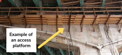 Image of the underside of the Gardiner Expressway West Deck that shows an example of an installed access platform. The access platform depicted is a wooden structure that is installed on the underside of the Expressway along the bent.